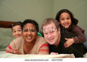 stock-photo-a-family-laying-together-on-a-large-bed-10473760